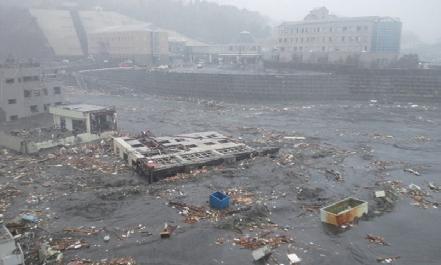 当時、海抜16mの地盤にあった町立病院(現:町地域医療センター。写真右上の建物)。大津波により1階部分が浸水した(平成23年3月11日)
